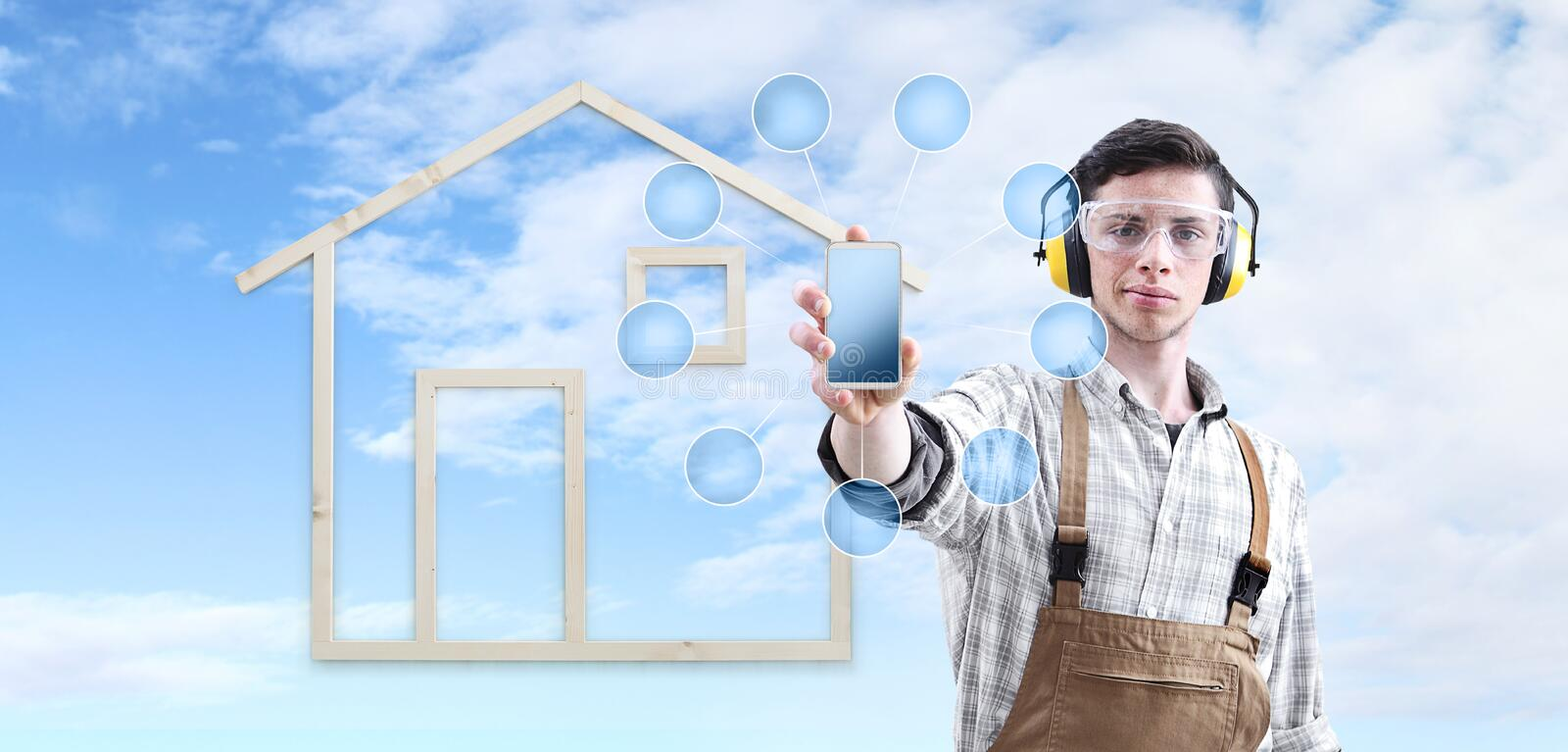 House construction renovation concept handyman carpenter man show the mobile phone with empty symbol icons, isolated royalty free stock photography