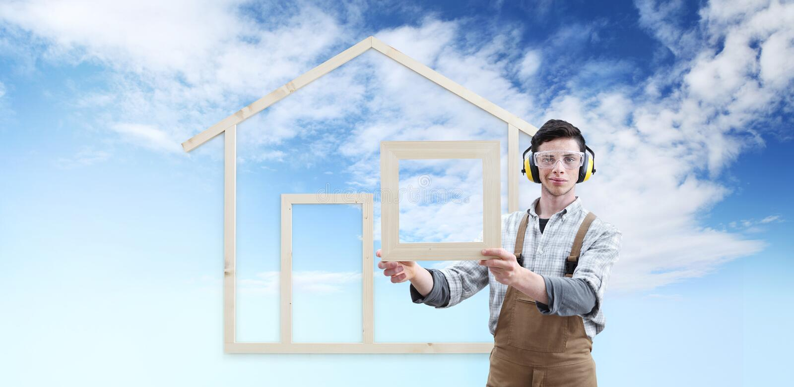 House construction renovation concept handyman carpenter man show the model of a wooden house isolated on blue sky background, stock photography