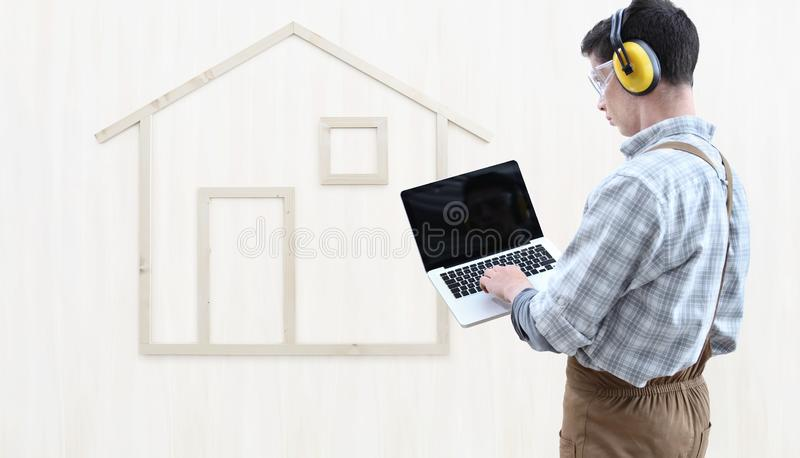 House construction renovation concept handyman carpenter man touch screen of digital tablet, isolated with the model of a wood stock photos