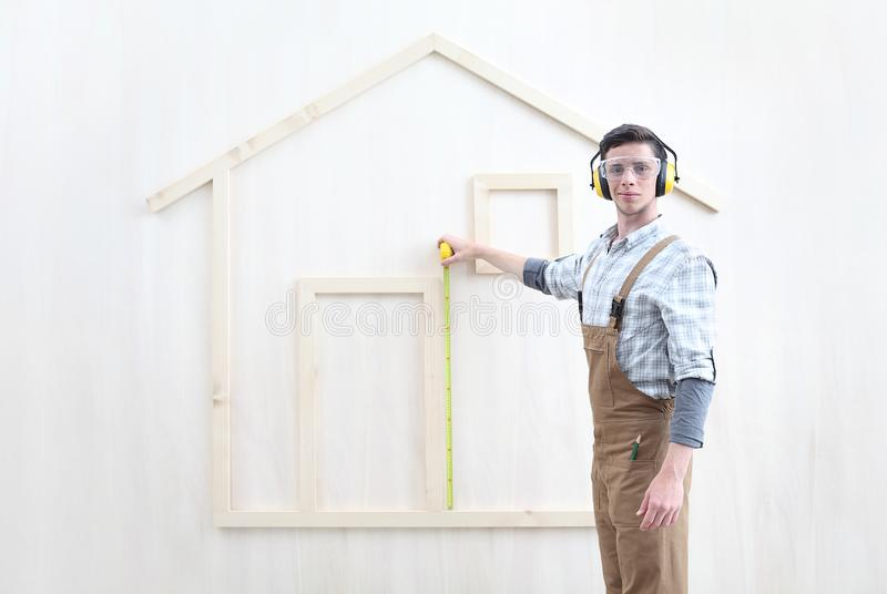 House construction renovation concept handyman carpenter worker man with meter  measure and show the model of a wooden house,. Custom solutions royalty free stock image