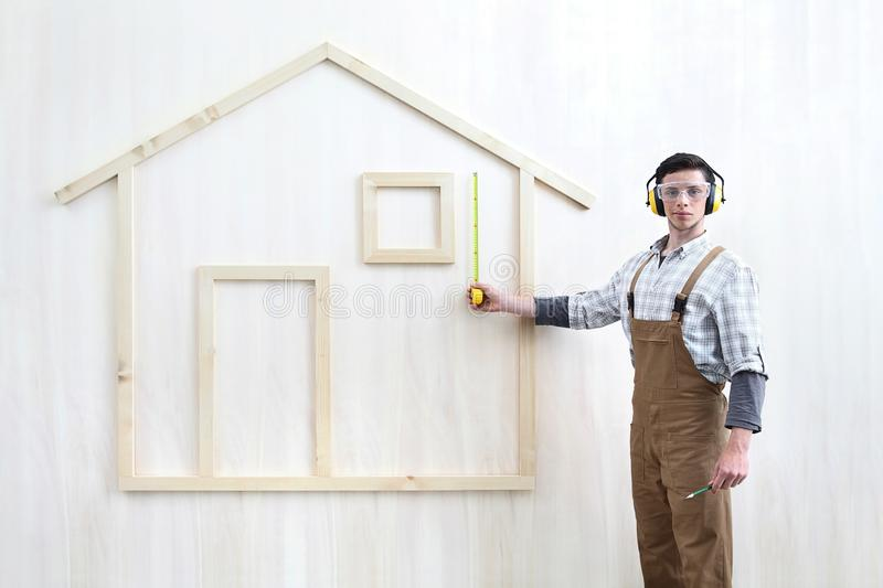 House construction renovation concept handyman carpenter worker man with meter  measure and show the model of wooden house, stock images