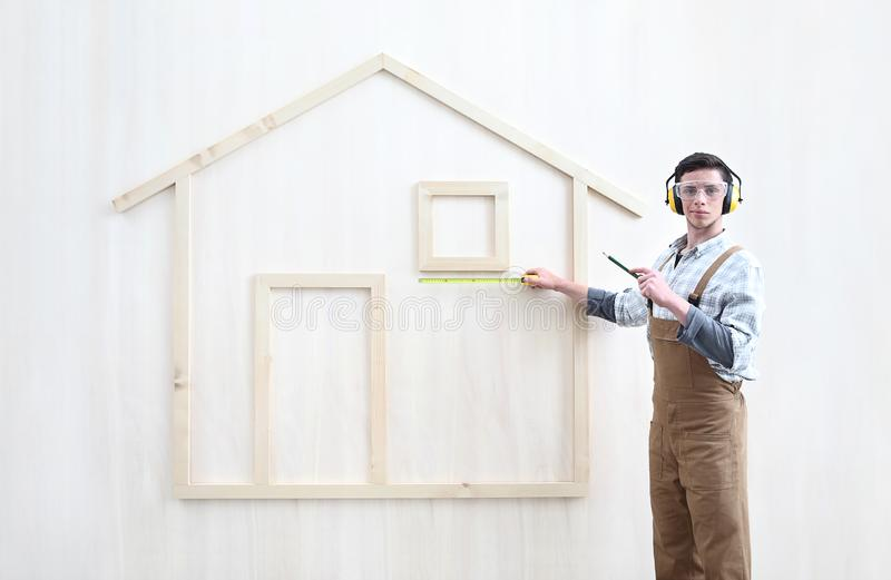 House construction renovation concept handyman carpenter worker man with meter  measure and show the model of a wooden house,. Custom solutions stock photography