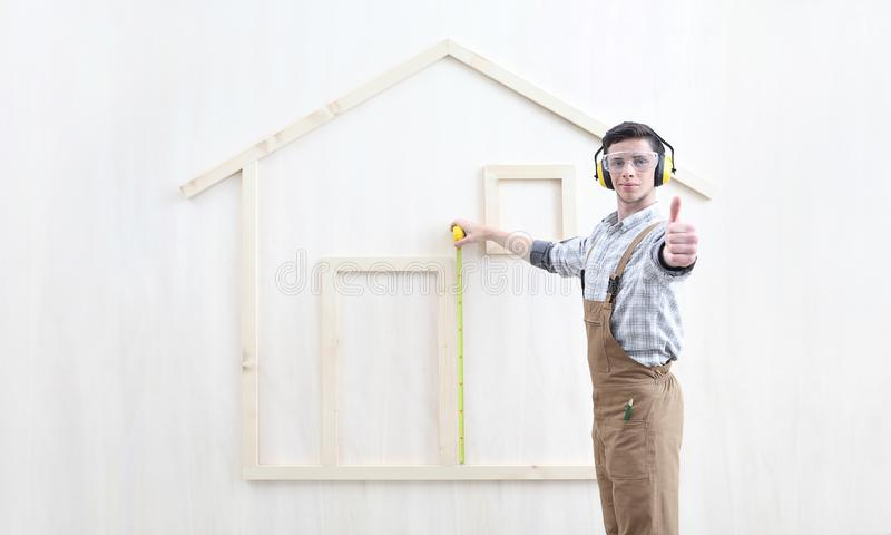 House construction renovation concept handyman carpenter worker man with meter  measure and show the model of a wooden house, like royalty free stock photo