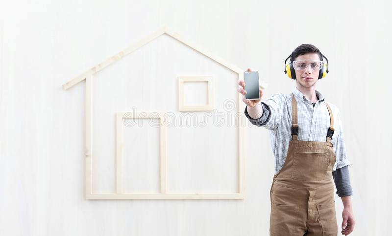 House construction renovation concept handyman carpenter worker man show the mobile phone isolated with the model of a wooden royalty free stock photo