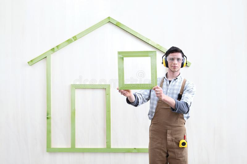 House construction renovation concept handyman carpenter worker man show the model of wooden green house royalty free stock image