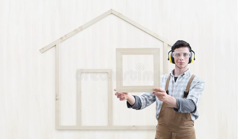 House construction renovation concept handyman carpenter worker man show the model of a wooden house isolated on wood. Background royalty free stock photography