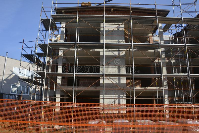 House construction scaffolding with orange mesh and blue sky stock photo