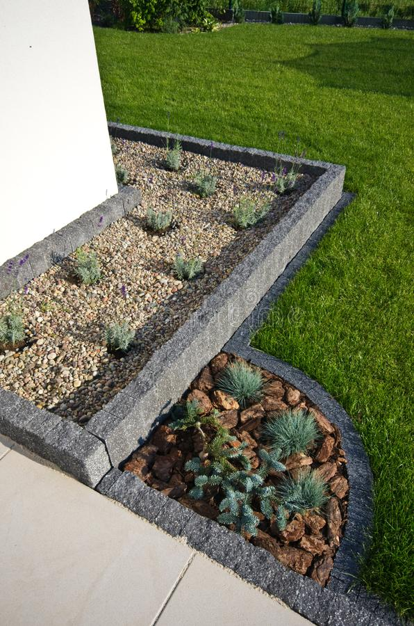 House corner design idea: stone framing as flowerbed, evergreens and lavender plants, terrace. A design for home exterior: corner wall and terrace detail, stone stock image