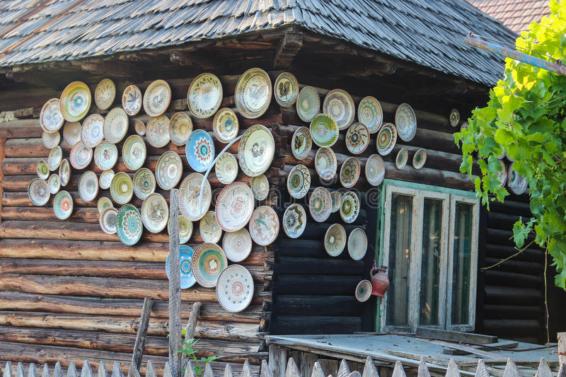 House Decorated with Ceramic Plates. Part of a traditional Romanian wooden house from Gorj county with walls decorated with ceramic pottery stock images