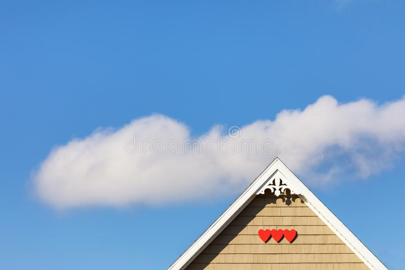 House detail with red hearts and cloud in the sky stock image