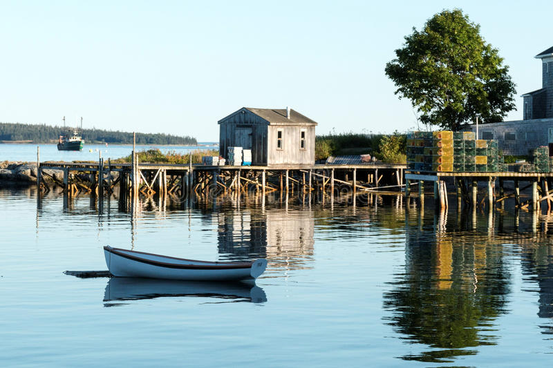 House, dock, row boat and lobster traps reflecting in the water stock photography