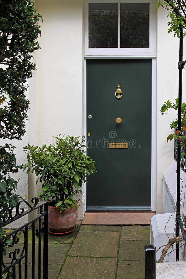 House door. Residential house doorway with green door and patio royalty free stock images