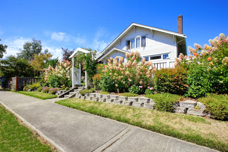 House with entance wooden archway and flower bed stock images
