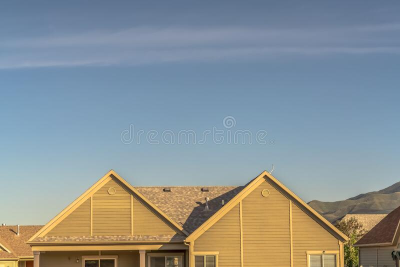 House exterior with close up of roof against mountain and blue sky background stock photography