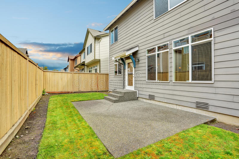House exterior with mocha siding. View of patio area with concrete floor. stock photography