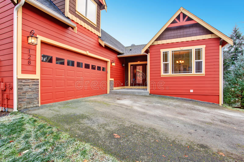 House exterior. Red clapboard siding house with stone wall trim. View of garage and entrance porch royalty free stock photo