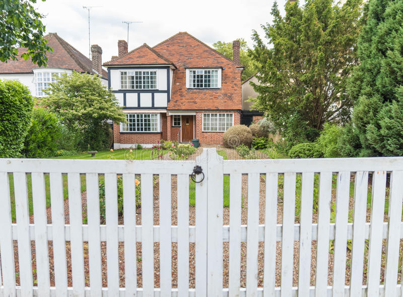 House exterior with white picket fence. Beautiful typical British house with white picket fence in London. May 2017 stock images