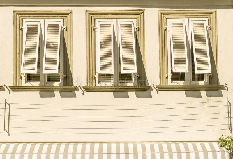 House facade with stucco 3 windows and unfolded wood shutters aw royalty free stock photo