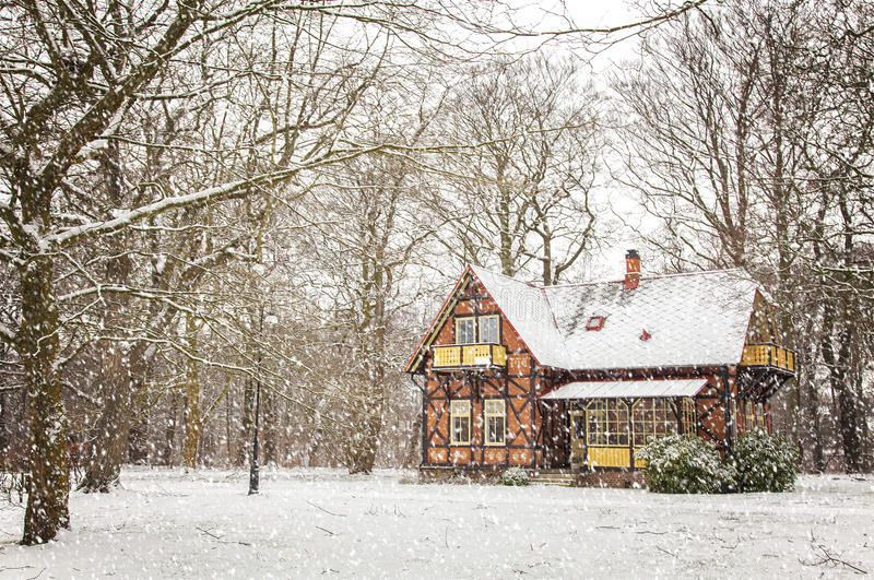 House in falling snow stock photography