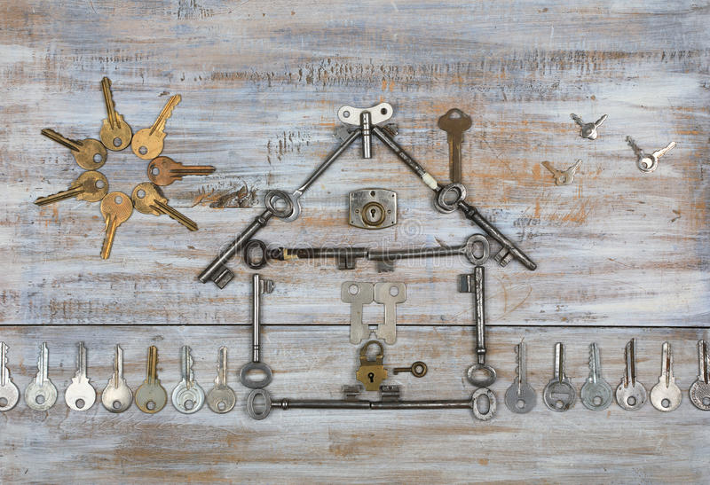 A house with a fence and the sun of antique keys. Background with a house shape with a fence and the sun made with old keys on old painted wooden boards. Top stock image