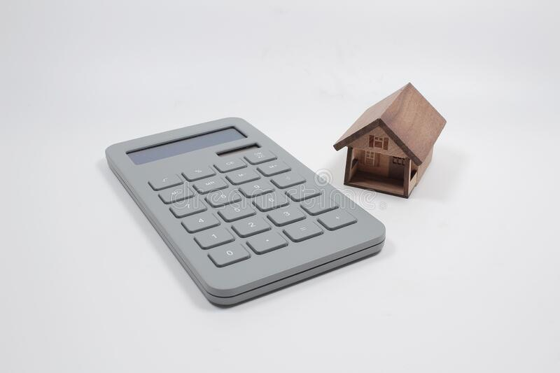 House figure with calculator  on background, closeup. Real estate agent service royalty free stock images