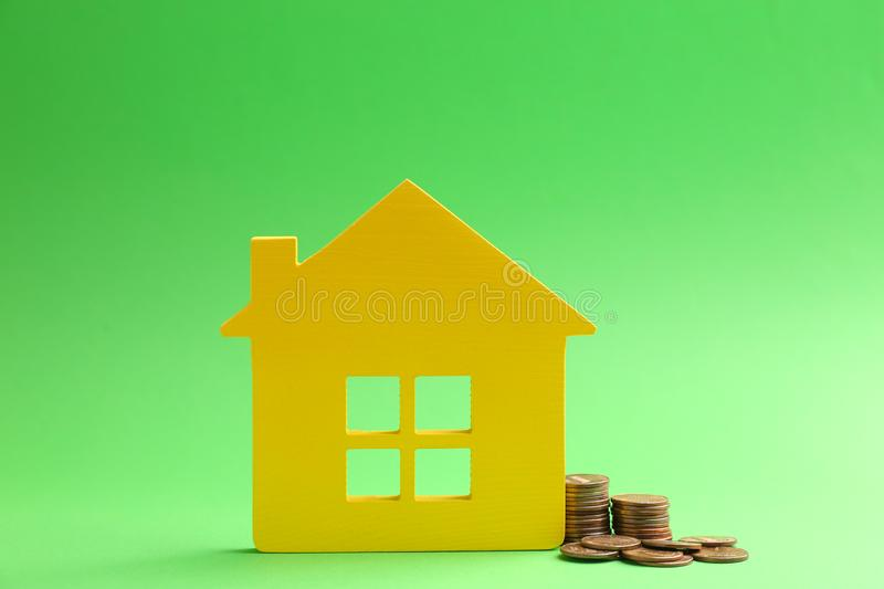 House figure and coins. On color background stock photo
