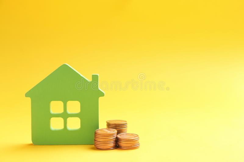 House figure and coins on color background. Space for text royalty free stock photography