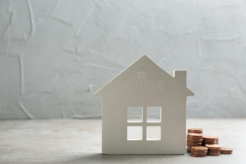 House figure and coins on table against grey background. Space for text royalty free stock photos