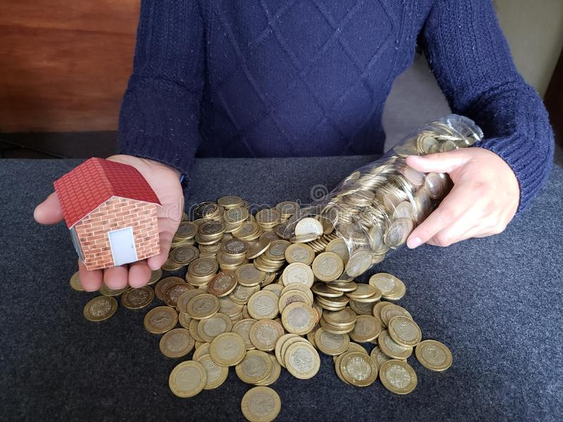 house figure in the hand of a person and coins of savings in mexican pesos stock images