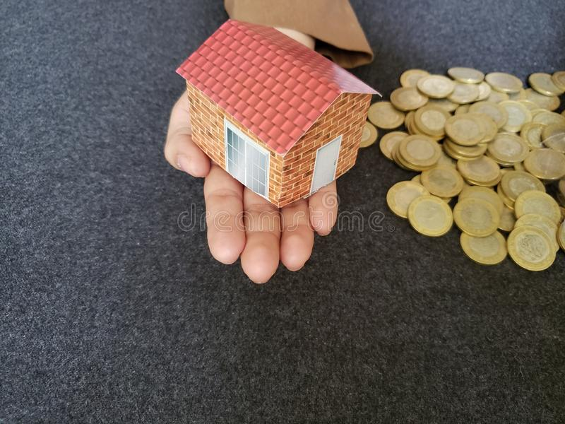 House figure in the hand of a person and coins of savings in mexican pesos. Trading and exchange, bank and commerce, price of buy and sell, cash value and money stock photo