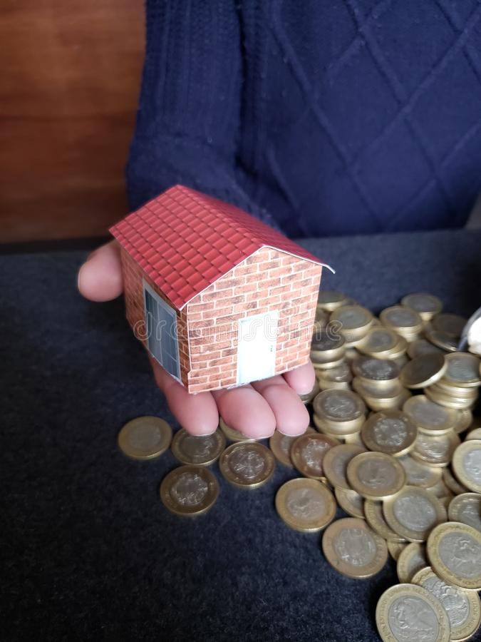 house figure in the hand of a person and coins of savings in mexican pesos royalty free stock images