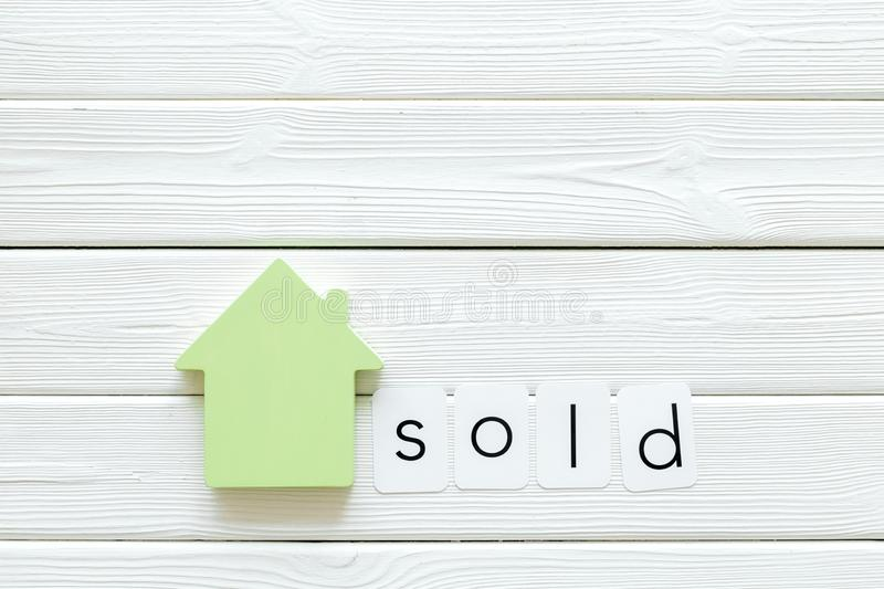 House figure and sold copy on office desk white wooden background top view mock-up. Buy house concept. House figure and sold copy on office desk white wooden royalty free stock photos