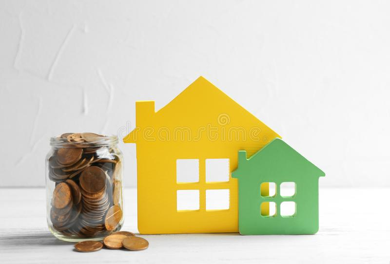 House figures and jar of coins on table. Against light background royalty free stock photos