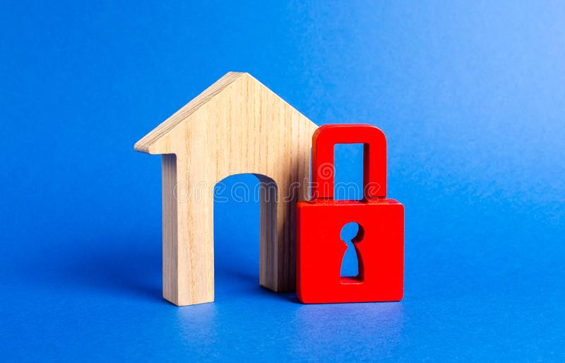 House figurine with large doorway and red padlock. Security and safety. Confiscation for debts. alarm system. seizure of property stock photo