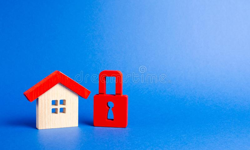 House figurine and a red padlock. Security and safety. Confiscation for debts. alarm system. seizure of property. Protection. Of property rights. Unavailable royalty free stock photos