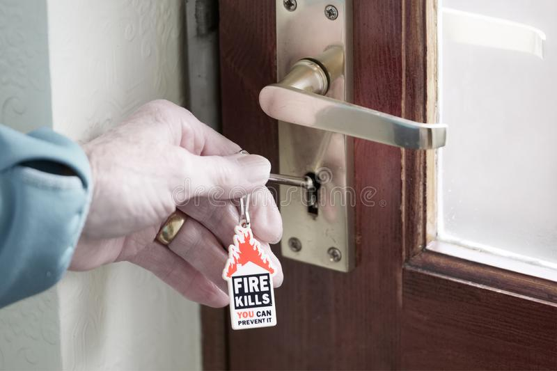 House fire kills symbol on key ring and senior person hand with key unlocking door to escape stock photo