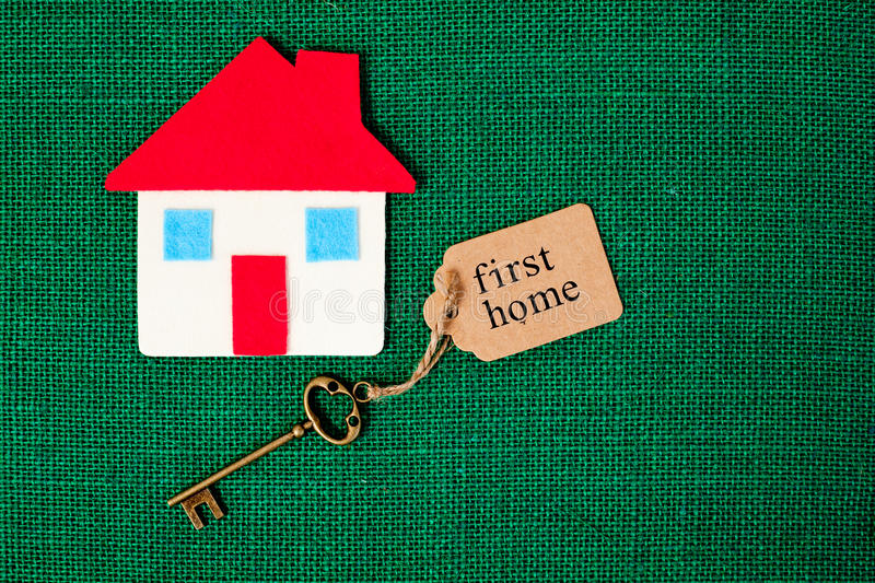 House - First Home. House with First Home key on green background royalty free stock photo
