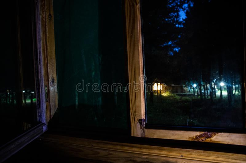 House in the forest at night. View from window. Selective focus. Long exposure shot royalty free stock photos
