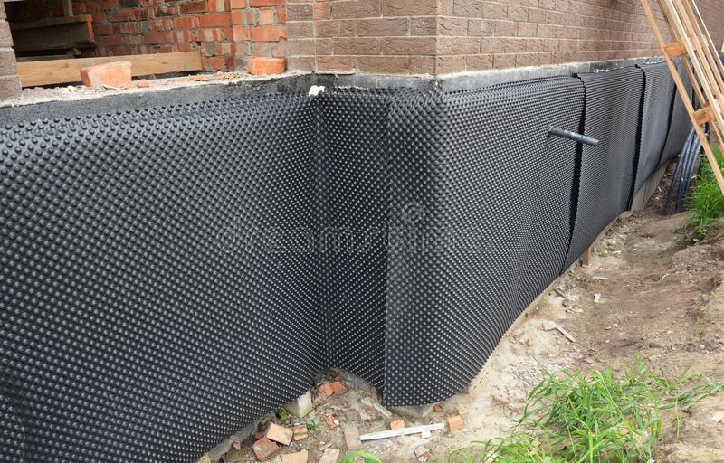 House foundation insulation details with waterproofing bitumen membrane, damp proofing. House foundation insulation, sewer pipe royalty free stock images