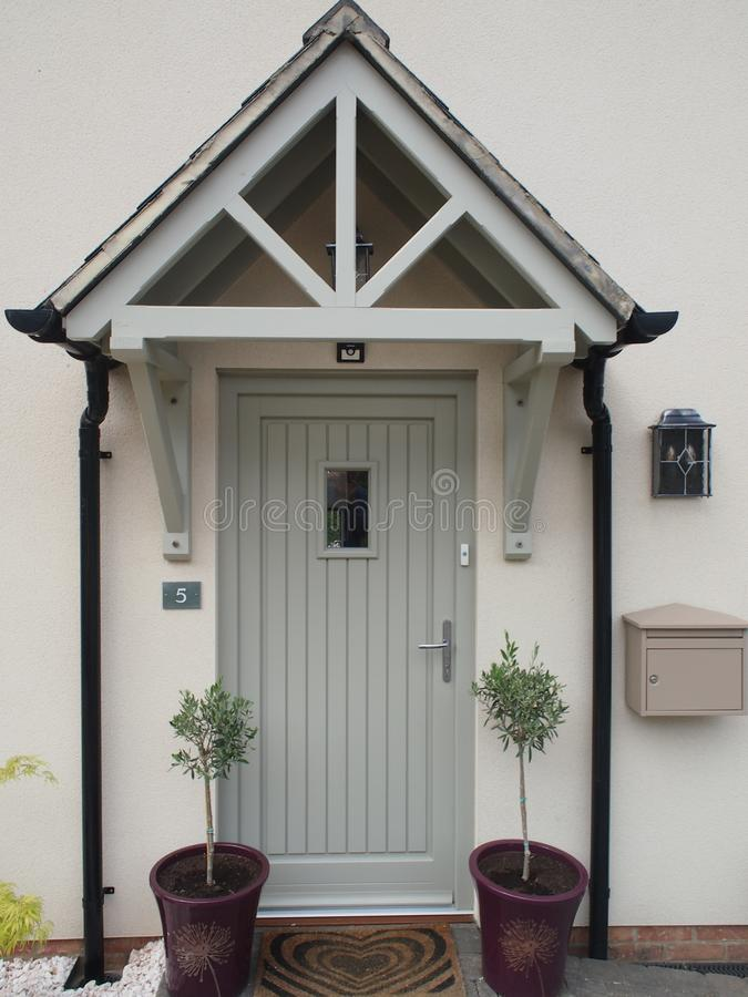 House front door with porch. Modern UK house front door with porch, outside light, letterbox, plants in pots either side stock photography