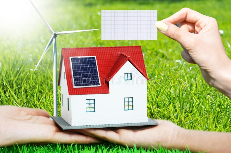 The house of the future with renewable energy sources and empty piece of paper as background, add copy or text stock photography