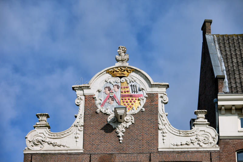 House Gable in Amsterdam. Ornate Dutch style neck gable with coat of arms on top of a 17th century house in the Old Town of Amsterdam, the Netherlands royalty free stock photography