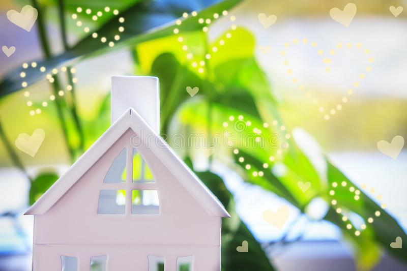 House on green background with heat bokeh. Home insurance concept stock image