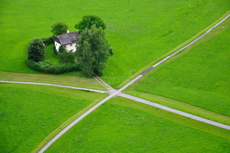 House in a green field, Salzburg, Austria stock photos