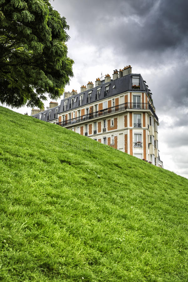 House on green hill. Against dark sky royalty free stock photography