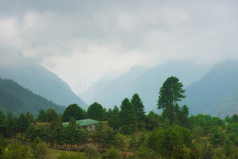 House on green hill with range of mountain and fog. Monsoon background stock photo