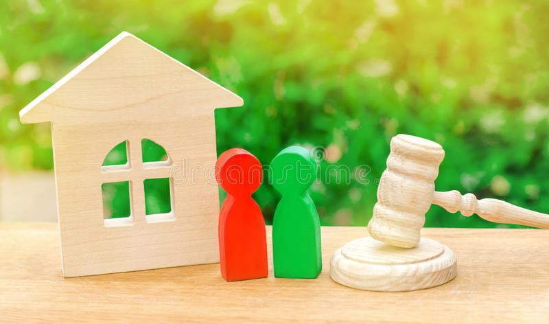 House, hammer of the judge with wooden figures of people. Clarification of ownership of property. Concept settlement stock photography