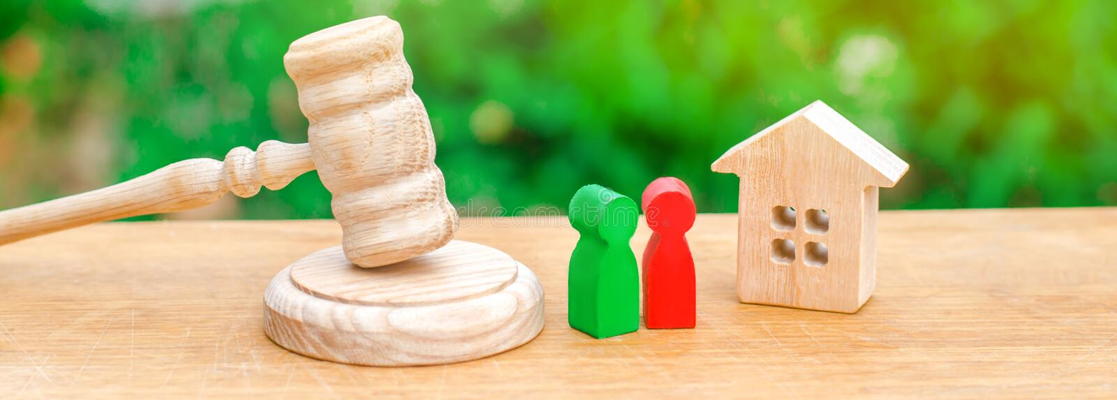 House, hammer of the judge with wooden figures of people. Clarification of ownership of property. Concept settlement of litigation stock photography