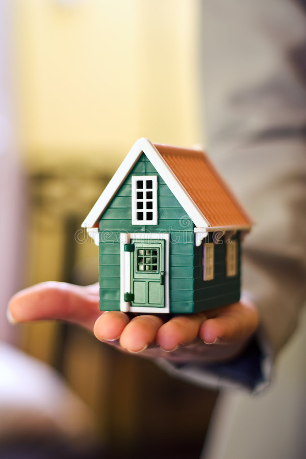 House in hand. Real estate business - woman holding a miniature house in hand stock photos