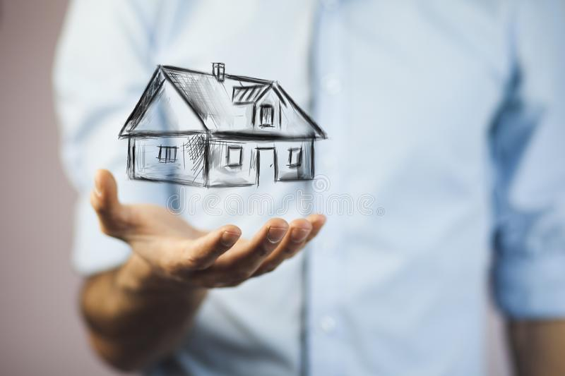 House on hand. Drawing house in man hands stock photography